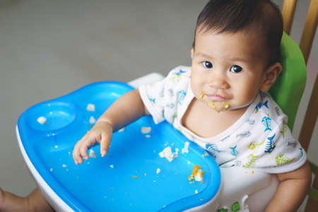 9 months old: 9 months old Asian baby eating food by himself Stock Photo