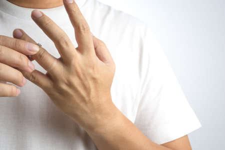 Man take off his wedding ring on white background