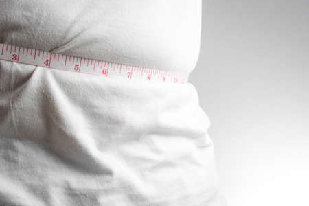 man measurement: Man measuring his fat belly with measurement tape