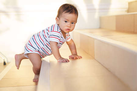 10 months adorable Asian baby development , climbing up stairs at home Stok Fotoğraf