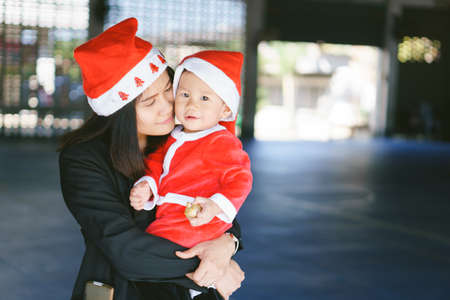Asian mother holding 11 months old baby in santa suit