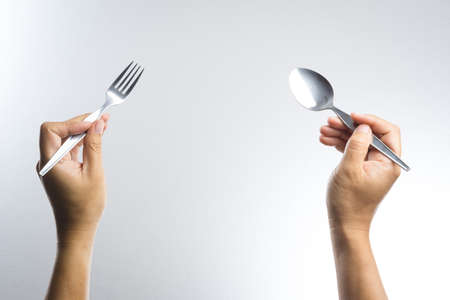 Man hand holding a silver fork and spoon on white background Stock Photo