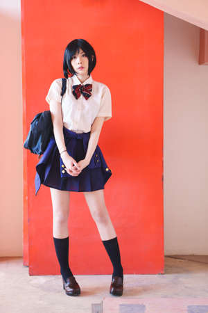 Charming Asian girl in student uniform on red background