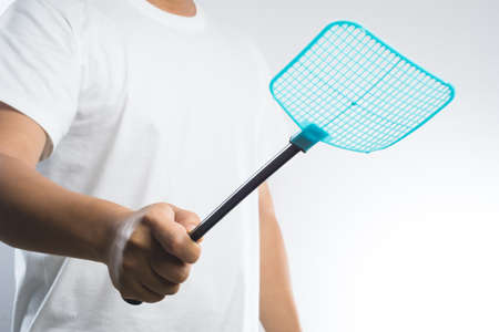 hand holding fly or insect swatter on white background