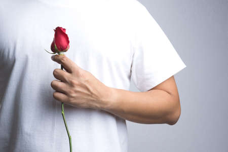 A man hand with red rose flower on white background