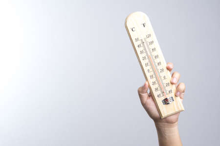 Hand holding classic thermometer on white background