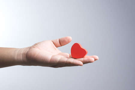 A man hand with wooden red heart object on white background