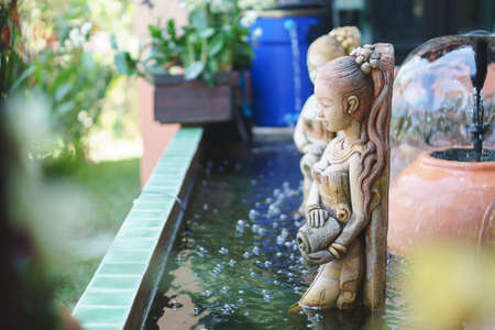 Common fountain sculpture of the Thai ancient woman in the pond Stock Photo
