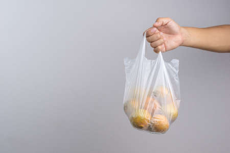 Hand holding plastic bag full of oranges on white background