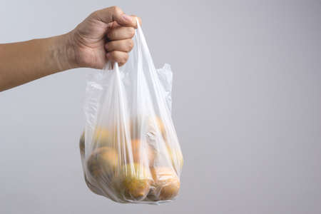 Hand holding plastic bag full of oranges on white background