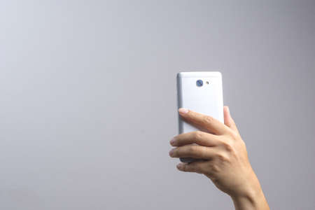 ploblem: Hand taking a photo or video by mobile phone on white background Stock Photo