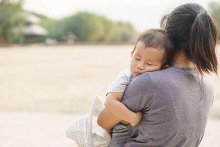 Slapende 1-jarige Aziatische baby vastgehouden door zijn moeder