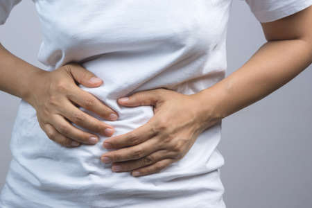 constipation symptom: Woman putting her hands for belly or stomach ache on grey background