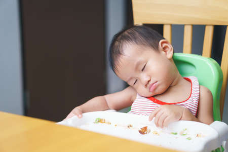 A year and 3 months Asian baby is sleeping while eating on high chiar Stock fotó