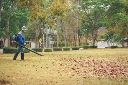 労働者は送風機によって公園で紅葉をきれい 写真素材