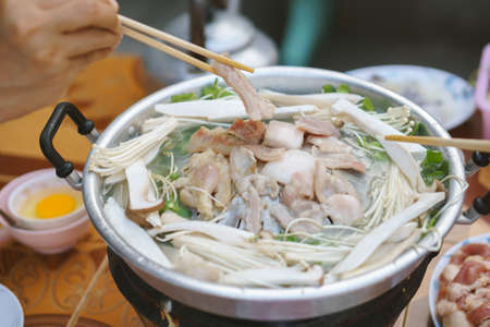 Thai common buffet, grill pork or barbecue on hot pan with vegetables and many foods Stock Photo