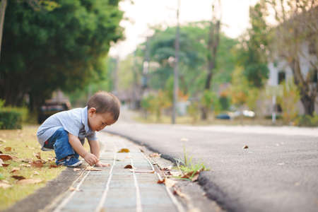 Asian boy about 1 year and a month learning to walk across the street Stock Photo
