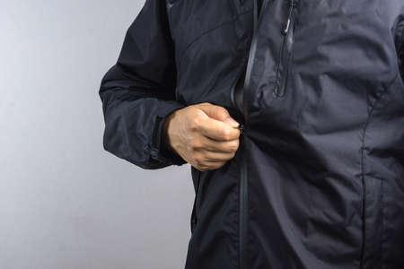 흰 배경에 검은 정전기 방지 또는 습식 재킷 또는 비옷을 착용하는 남성 스톡 콘텐츠