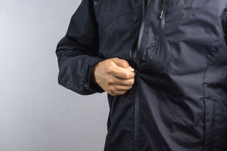 Man wearing black anti static or wet weather jacket or rain coat on white background
