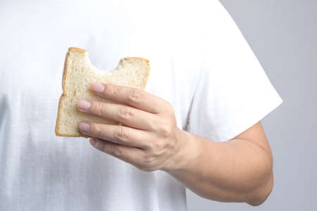 sprouted: Hand holding sliced whole grain bread with bite mark on white background