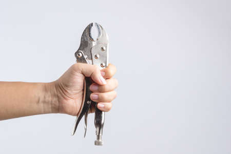 Hand holding locking pliers or mole grips on white background