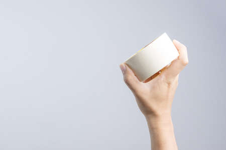 Hand holding paper tape roll on white background Stock Photo
