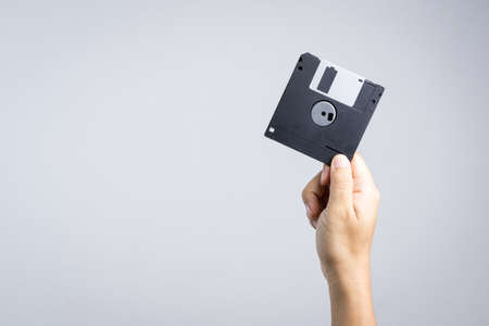 Hand holding floppy disk on white background