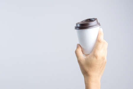 Hand holding hot coffee paper cup on white background Stock Photo