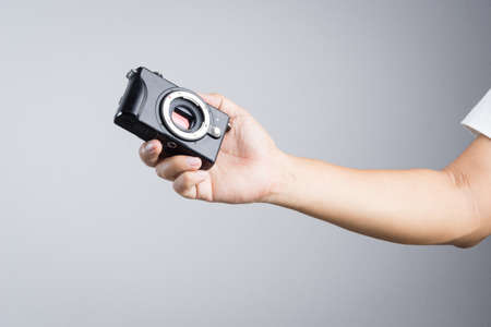 Hand holding mirrorless camera with micro 43 sensor  on white background Editorial