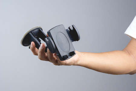 Hand holding phone holder mount for safety use in car on white background