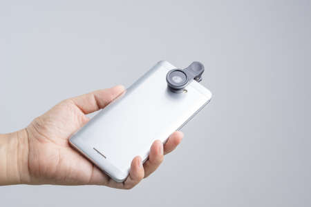 shutter: Hand holding smart phone equipped with extension lens on white background