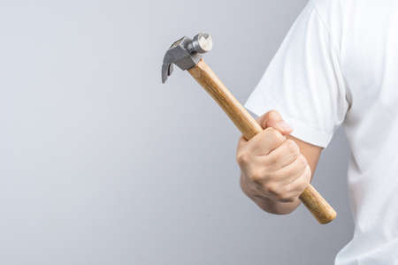 rusty nail: Hand holding custom wooden grip hammer on white background Editorial