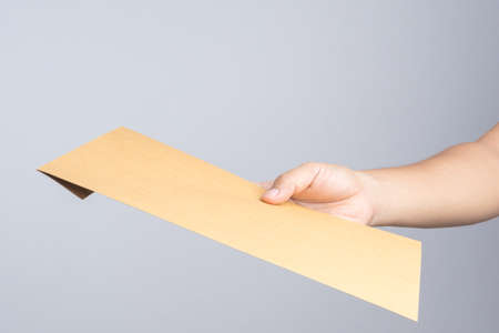 Hand holding a self sealing brown envelope document on white background