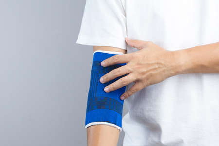 elbow band: Arm with elastic elbow support and hurt gesture on white background
