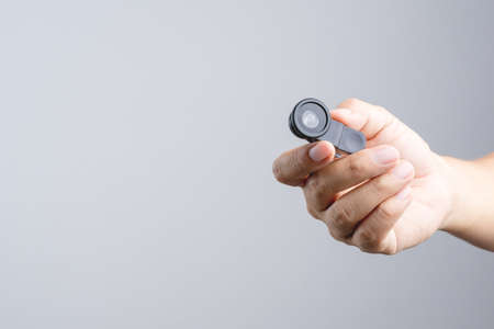 shutter: Hand holding with extension lens for smart phone camera on white background