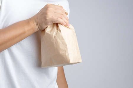 Hand holding crumble brown paper bag panic as a tool for relieving panic attack or being nauseated as Hyperventilation syndrome on white background