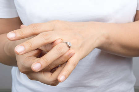 Woman put on her wedding ring on grey background Stock Photo