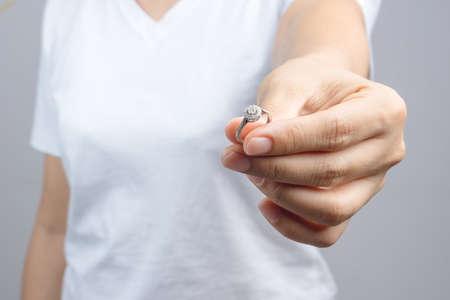Woman return her wedding ring on grey background Stock Photo