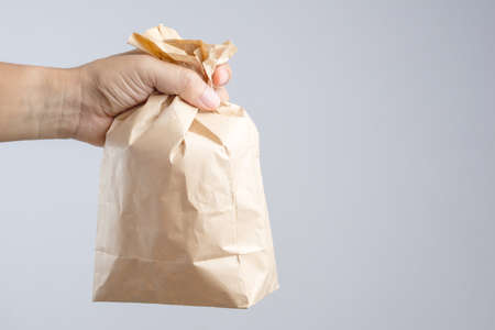 unease: Hand holding crumble brown paper bag panic as a tool for relieving panic attack or being nauseated as Hyperventilation syndrome on white background
