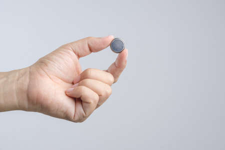Hand holding round lithium button cell battery on white background Zdjęcie Seryjne