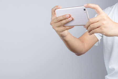 ploblem: Hand taking a photo or video by mobile phone on white background Editorial