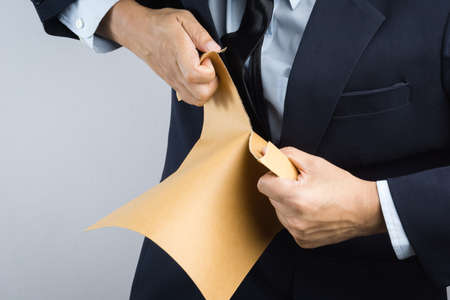 Business man hand tearing self sealing brown envelope document in anger on white background