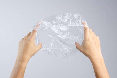 Hand die beschikbare transparante plastic douchekap op witte achtergrond houdt Stockfoto
