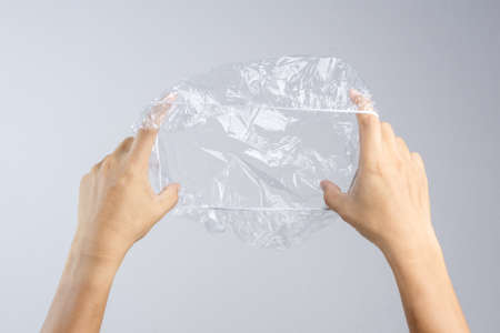 Hand holding disposable transparent plastic shower cap on white background