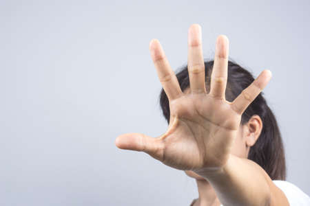 Woman hand doing a stop gesture on grey background 免版税图像 - 87277810