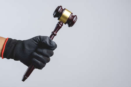 criminal: Hand wearing black glove holding wooden judges gavel as a illegal or injustice sign on white background