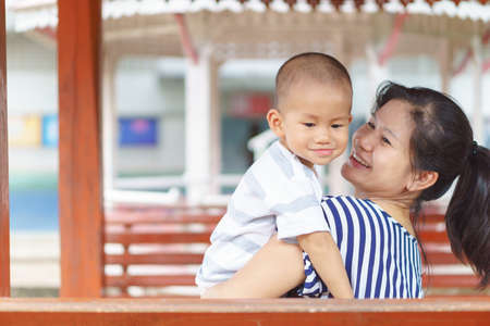 1 year old and 7 months Asian baby being held by his mother Stock Photo