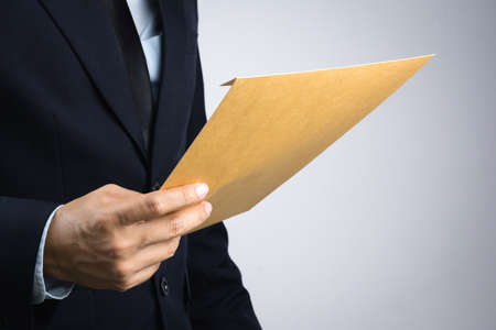 Business man hand holding a self sealing brown envelope document on white background Stock Photo