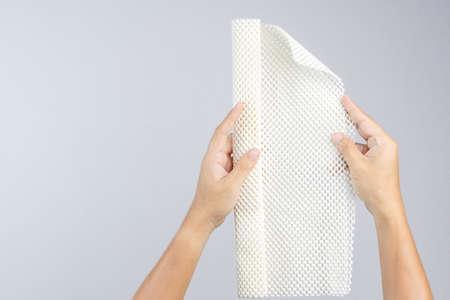 Hand holding white anti slip rubber mat for bathroom or wet floor on white background