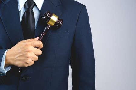 La mano dell'uomo di affari che tiene il martelletto di legno del giudice come legge o giustizia firma su fondo bianco Archivio Fotografico - 88656912